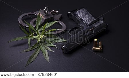Cannabis Leaves Marijuana, Weapons And Handcuffs On Dark Background