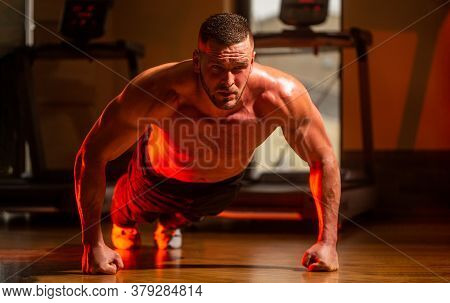 Man Doing Push-ups. Muscular And Strong Guy Exercising. Slim Man Doing Some Push Ups A The Gym. Musc
