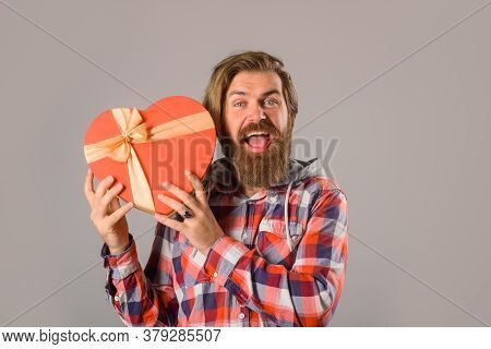 Bearded Man In Casual Style Holds Gift Box. Man Holds Valentines Gift Box In Shape Of Heart. Time Fo