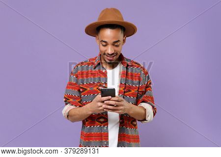 Smiling Young African American Guy In Casual Colorful Shirt Hat Posing Isolated On Violet Wall Backg