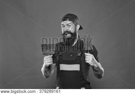 Plasterer Hipster Builder In Cap Red Background. Interior Designer. Bearded Man Worker With Plasteri