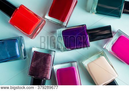Group Of Bright Colored Nail Polishes On A Blue Background. Set Of Decorative Cosmetics For Body Car