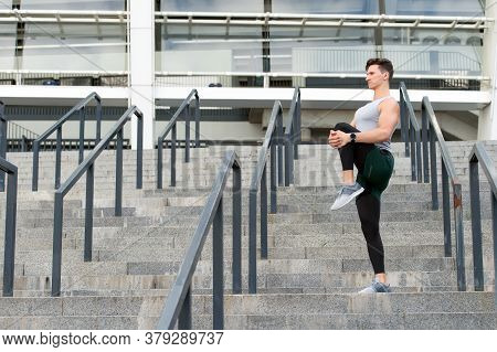 Keeping Those Muscles Flexible. Young Male Runner Athlete Training And Exercising Outdoors In The Ci