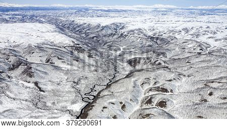 Panorama Of Snow-capped Mountains From A Helicopter. The Landscape Created By Volcanic Activity On T