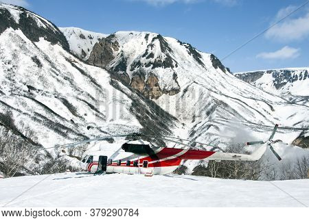 The Helicopter Is Sitting In The Snow In A Mountainous Area. Rotorcraft On A Wild Helicopter Pad In