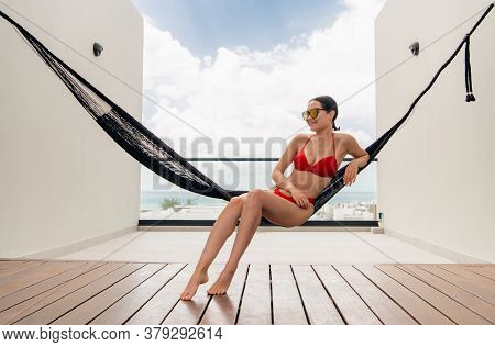 Woman In Red Bikini Resting In Hammock With Ocean View On Rooftop Of A Luxury Hotel.