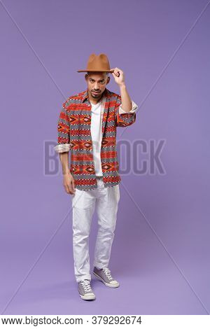 Puzzled Young African American Guy In Casual Colorful Shirt Hat Posing Isolated On Violet Background