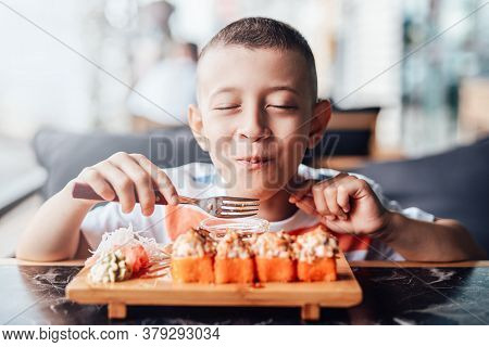Boy With Great Pleasure Eats Sushi In Outdoor Cafe. Close-up Portrait, Bright And Colorful Image