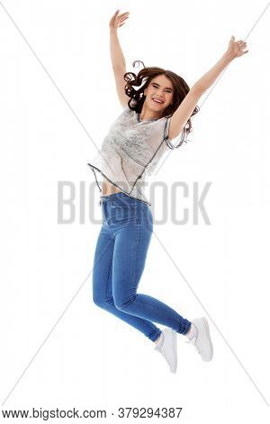 Young happy and smiling woman jumping on white background.