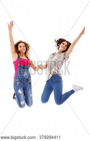 Young happy and smiling two womans jumping on white background.