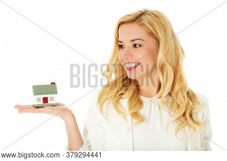 Young businesswoman showing house models on her hand.