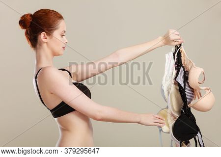 Bosom Concept. Slim Attractive Red Hair Woman Wearing Black Underwear Holding Many Bras In Hand, Cho