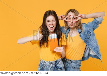Two Funny Young Women Girls Friends In Casual T-shirts Denim Clothes Isolated On Yellow Background.