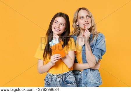 Two Pensive Young Women Girls Friends In Casual T-shirts Denim Clothes Isolated On Yellow Background