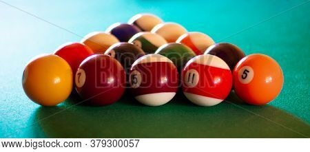 Triangle Of Multicolored Billiard Balls With Numbers On The Pool Table. Sports Game Billiards On A G