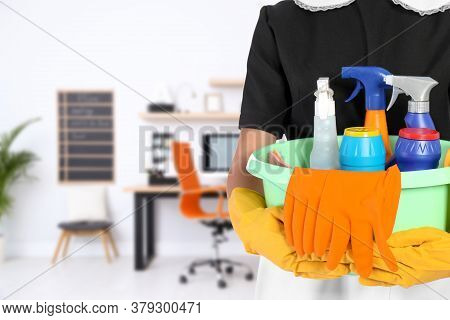 Young Chambermaid Holding Plastic Basin With Detergents In Office, Closeup. Space For Text