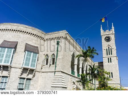Parliament government building and clocktower with Barbadian flag is located on Broad Street in Bridgetown in Caribbean island Barbados