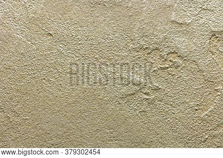 Golden Messy Wall Stucco Texture. Closeup Decorative Plaster Paint For Background.