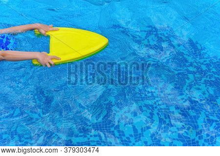 Kid Learning Swimming With A Floating Pad On A Swimming Pool