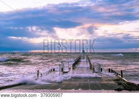 Beautiful Sunset Over Foreshore With Big Waves And Boat Jetty
