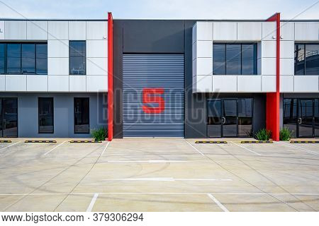 Industrial Building With Empty Parking Lot. Closed Warehouse Door With Large Number 5 Painted On It.