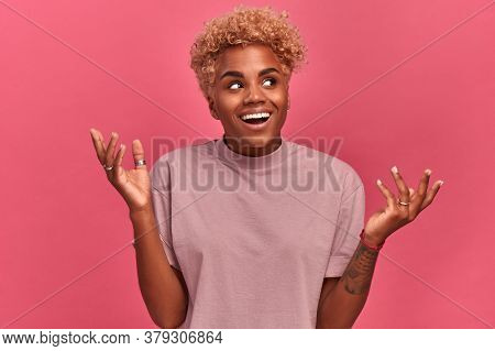 Woman Of African American Descent Looks Excited Happy On A Pink Background In The Studio. Girl Is Pl
