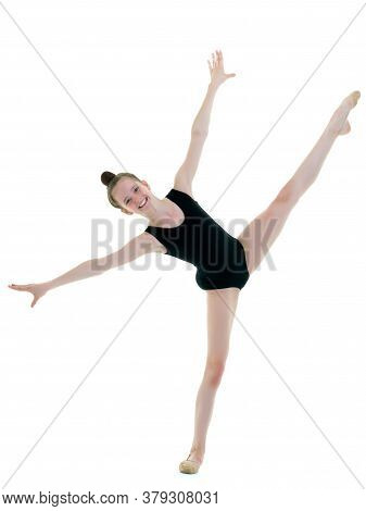 A Girl Gymnast Performs An Acrobatic Element. The Concept Of Childhood, Sport, Healthy Lifestyle. Is
