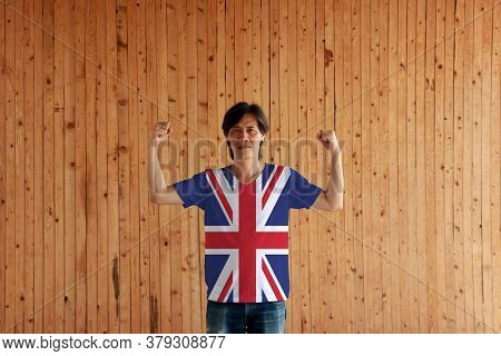 Man Wearing Union Jack Flag Color Of Shirt And Standing With Raised Both Fist On The Wooden Wall Bac