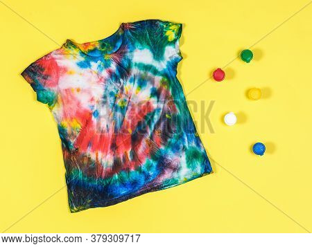 Tie Dye T-shirt And Colorful Paint Cans On A Yellow Background. White Clothes Painted By Hand. Flat