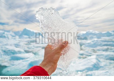 Global warming, climate change and Environmental protection concept with icebergs on Greenland. Hand holding melting ice by giant iceberg in Ilulissat icefjord on Greenland. Save the climate.