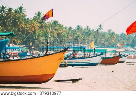 Canacona, Goa, India. Fishing Boats With Flags Parked On Famous Palolem Beach In Summer Sunny Day.