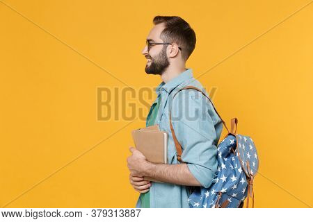 Side View Of Smiling Man Student In Casual Clothes Glasses Backpack Hold Books Isolated On Yellow Ba