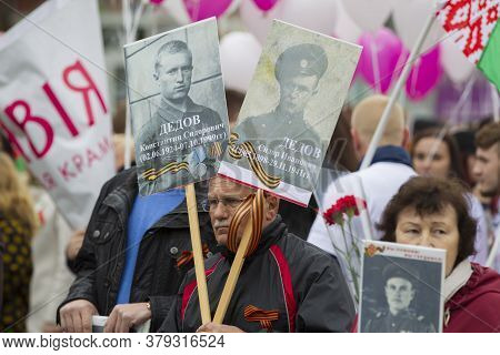 Belarus, The City Of Gomil, May 9, 2019. Victory Day. Immortal Regiment. A Man With Portraits Of Rel