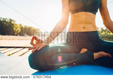 Partial View Of Sportswoman Meditating On Wooden Platform At Sunrise. Concept Of Healthy Lifestyle