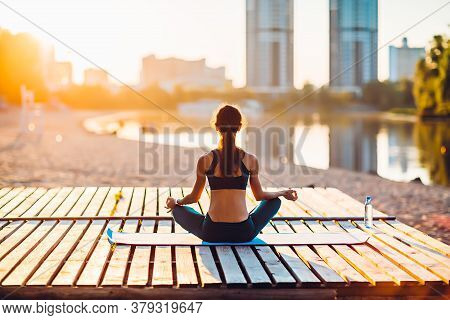 Back View Of Sportswoman Meditating On Wooden Platform At Sunrise. Concept Of Healthy Lifestyle