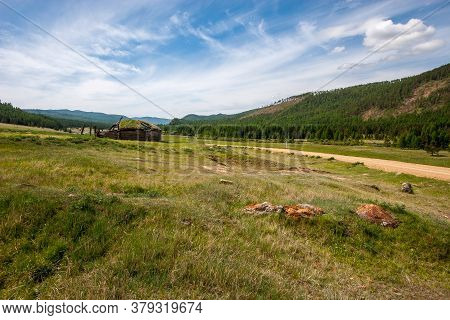 A Dirt Road Between The Hills And A Ruined Old Yurt On The Grass. Overgrown With Grass Hut. Clouds O