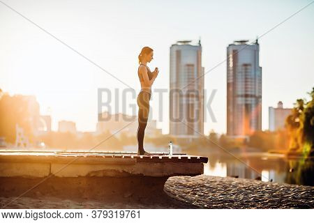Sportswoman Do Yoga On Wooden Platform At Sunrise. Concept Of Healthy Lifestyle