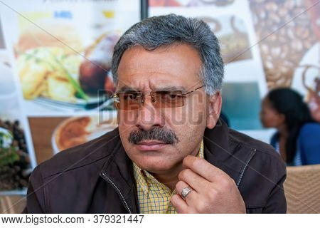 angry married Iranian man with sunglasses sitting down on the terrace of a coffeeshop