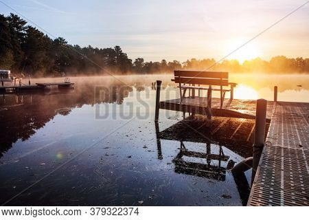 Fog over lake at sunrise from a dock during autumn