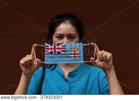 A Woman With Fiji Flag On Hygienic Mask In Her Hand And Lifted Up The Front Face On Brown Background