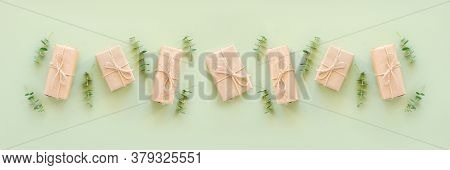 Row Gift Boxes Wrapped In Kraft Paper, Tied With Jute Twine And Natural Twigs Of Eucalyptus On Green
