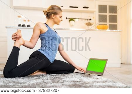 White caucasian fit sporty woman doing yoga king pigeon pose while working at home with laptop in living room while quarantine. Workout fitness sport healthy lifestyle and work from home concept.