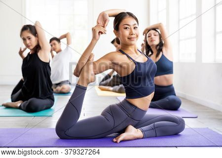 Portrait of asian yoga instructor coach wearing sportswear bra pants do king pigeon pose in yoga studio with her students in background. Work out fitness healthy lifestyle concept.