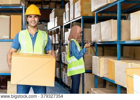 Portrait of Indian warehouse worker hold cardboard box packaging with muslim asian worker do inventory in warehouse distribution center environment. Using in business warehouse and logistic concept.