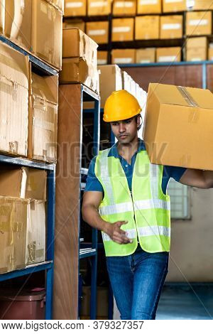 Portrait of Indian asian warehouse worker hold cardboard box packaging on his shoulder in warehouse distribution center environment. Using in business warehouse and logistic concept.