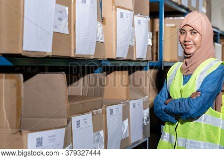 Portrait of Islam Muslim female warehouse worker crossed arm in front of product shelf with stock card in warehouse distribution environment. For business warehouse inventory and logistic concept.