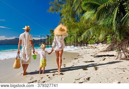 Family on beautiful Anse Soleil beach, young couple in white with three year old toddler boy. Summer vacation at Seychelles, Mahe.
