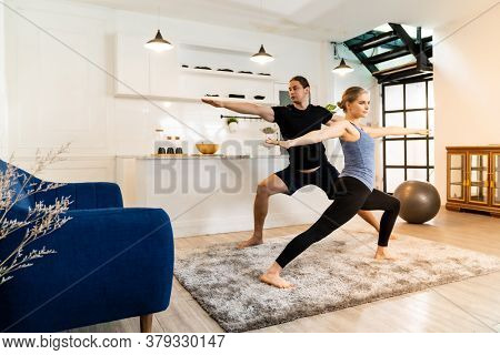 White caucasian fit sporty couple doing yoga warrior pose in living room at home. Working out, fitness sport and healthy lifestyle concept.