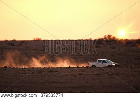 An image of a car on a dusty unsealed road in sunset light mood