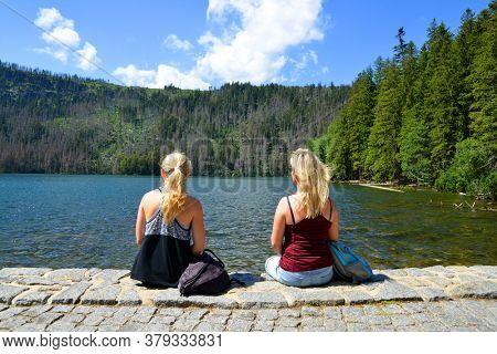 Two women sitting by Black lake (Cerne jezero) in the National park Sumava, Czech Republic.